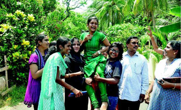 Kaavya's classmates lift her on hearing about her marks in Chennai on Thursday.— DC