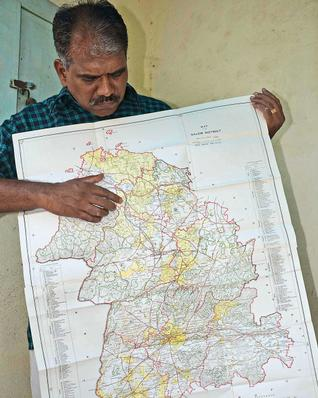 J. Barnabas, general secretary of the Salem Historical Society displays the century-old map of Salem district.– Photo: E. Lakshmi narayanan