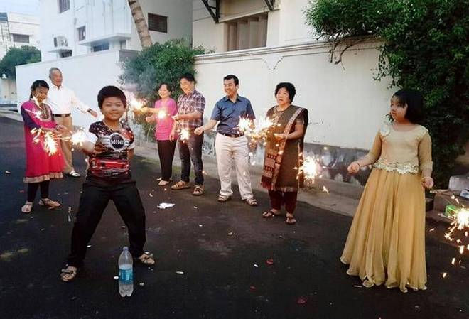 Members of the Min family bursting crackers to signal the arrival of New Year. | Photo Credit: R. Vimal Kumar