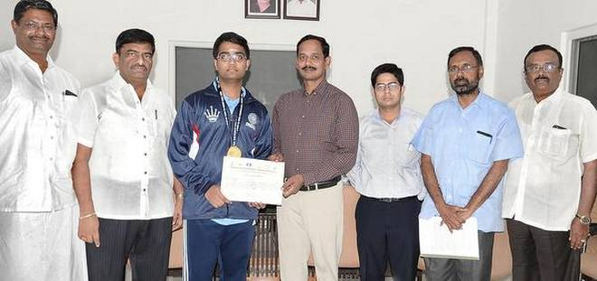 Erode Collector S. Prabhakar (centre) felicitating P. Iniyan for winning the World Youth Chess Olympiad.Special Arrangement